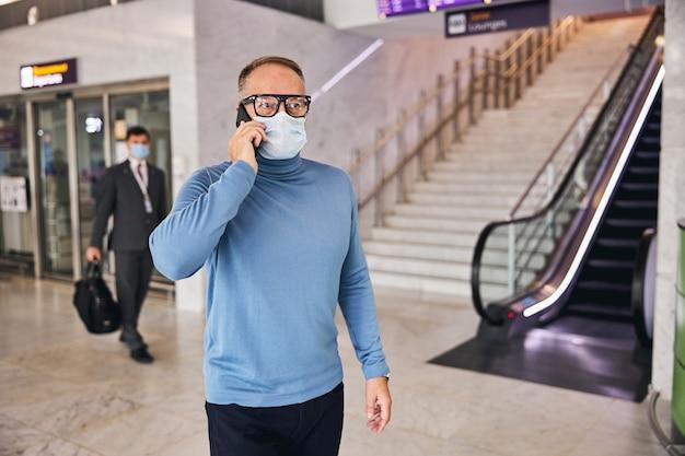 Uomo d'affari con una maschera facciale che fa una telefonata
