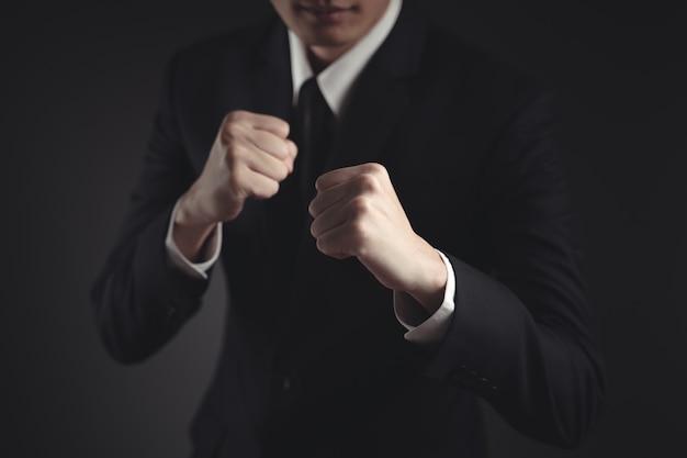 Uomo d'affari lotta e vincere in abito nero su fondo nero