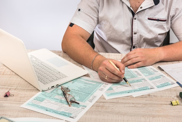 L'uomo d'affari compila il modulo fiscale 1040 con laptop e calcolatrice