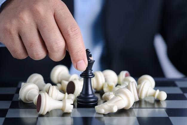 Le mani del dito dell'uomo d'affari controllano il re degli scacchi alla posizione di successo sul gioco di affari della concorrenza con gli scacchi nemici che cadono