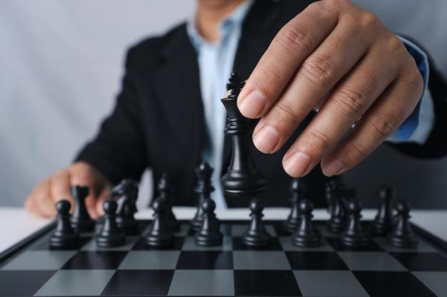 Mani del dito dell'uomo d'affari con la squadra dietro seduto e spostando il re degli scacchi alla posizione di successo