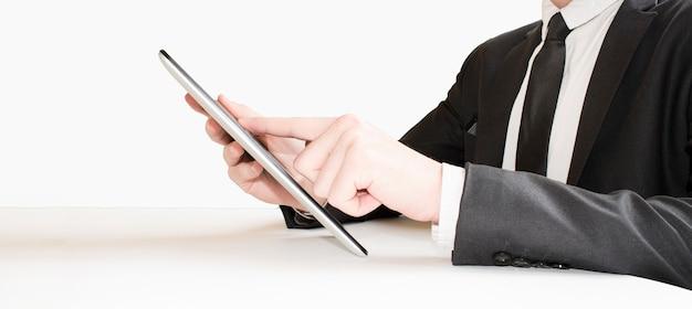 Dito dell'uomo d'affari che tocca lo schermo di una tavoletta digitale al gate di partenza di un aeroporto