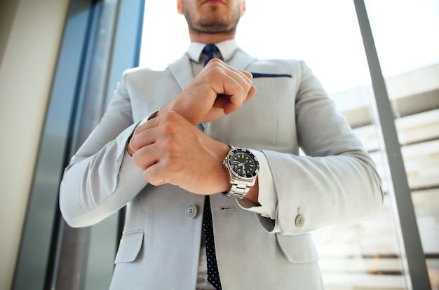 Uomo d'affari che fissa i gemelli del suo vestito. lo stile dell'uomo. vestito, camicia e polsini