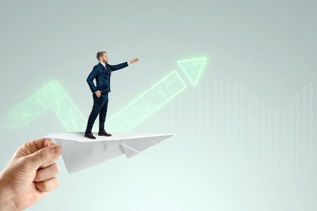 Uomo d'affari che vola su un aeroplano di carta con la mano che spinge di un investitore