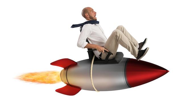 Uomo d'affari che vola sopra un razzo. aumenta la scalata al concetto di successo