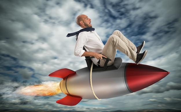 Uomo d'affari che vola sopra un razzo nel cielo. aumenta la scalata al concetto di successo