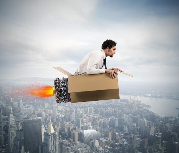 Uomo d'affari che vola con un missile di cartone con il fuoco nel cielo