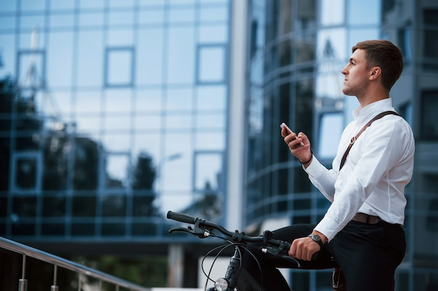 L'uomo d'affari in abiti formali con la bicicletta nera è in città.