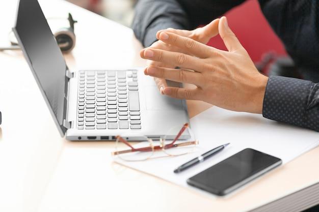 Un uomo d'affari davanti al monitor di un laptop durante una consultazione online con un ispettore fiscale. primo piano di mani, telefono e accessori.