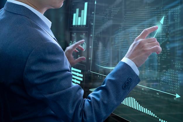 Uomo d'affari davanti al moderno touch screen virtuale che analizza sulla gestione del rischio di investimento e sul ritorno sull'analisi degli investimenti o sulle prestazioni aziendali.