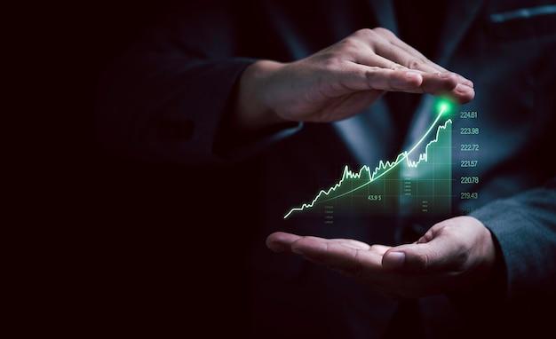 Gesto dell'uomo d'affari che protegge il grafico e il grafico di investimento virtuale in aumento per la tendenza dell'analisi del mercato azionario e il concetto tecnico del trader.