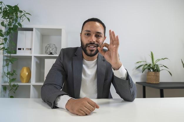 Uomo d'affari che gesticola bene uomo afroamericano in ufficio a casa che guarda la telecamera durante una videochiamata