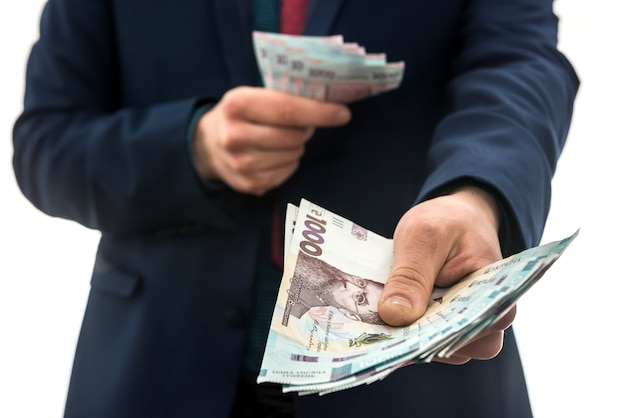 L'uomo d'affari dà una tangente o paga, in isolamento. uah. 1000 nuove banconote denaro ucraino