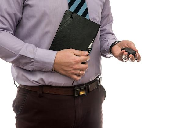 L'uomo d'affari dà le chiavi della macchina all'auto isolata sulla parete bianca