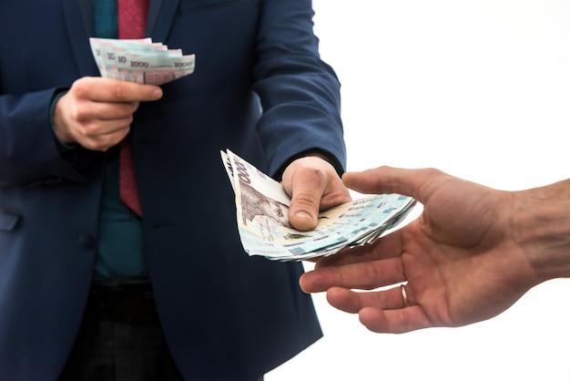 L'uomo d'affari dà o prende una tangente di denaro. grivna ucraina, nuove banconote da 1000 grivna. salva o concetto di corruzione.