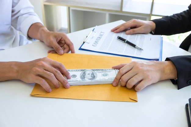 Uomo d'affari che dà tangenti soldi nella busta del loro partner per dare successo al contratto di affare