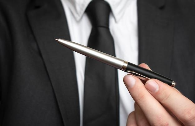 Uomo d'affari che dà penna per la tua firma negli appunti