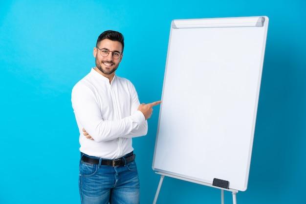 Uomo d'affari che dà una presentazione sul bordo bianco che dà una presentazione sul bordo bianco e che lo indica