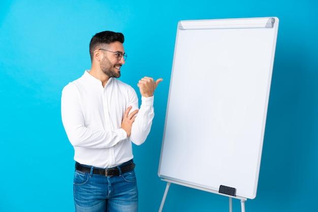 Uomo d'affari che dà una presentazione sul bordo bianco che dà una presentazione sul bordo bianco e che indica il lato