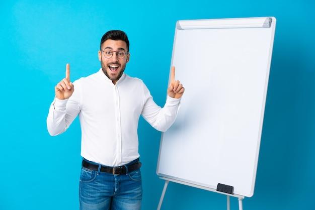 Uomo d'affari che dà una presentazione sul bordo bianco che dà una presentazione sul bordo bianco e che indica su