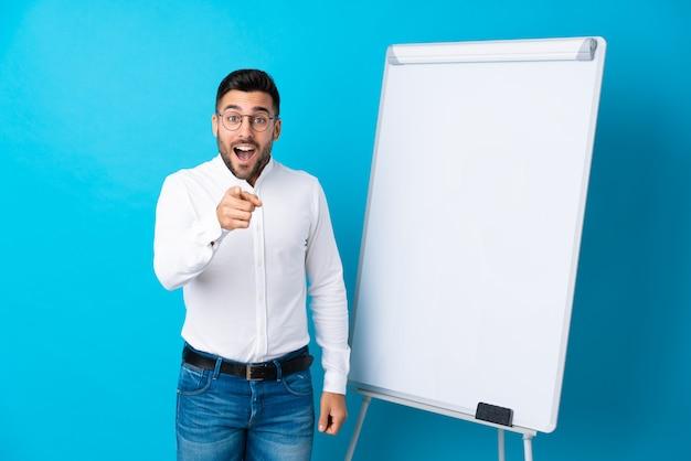 Uomo d'affari che dà una presentazione sul bordo bianco che dà una presentazione sul bordo bianco e sorpreso mentre indicando parte anteriore
