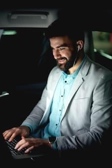 Uomo d'affari che va a casa guidando in macchina che lavora fino a tardi parlando di conversazione online.