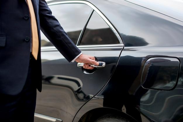 Uomo d'affari che entra nella sua auto
