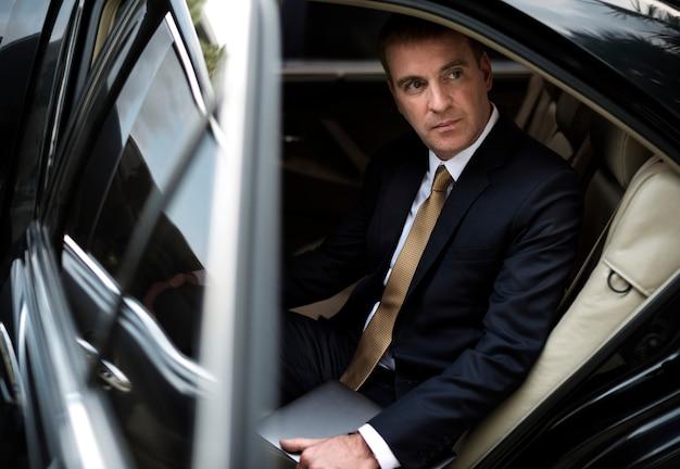 Uomo d'affari che esce dalla sua auto