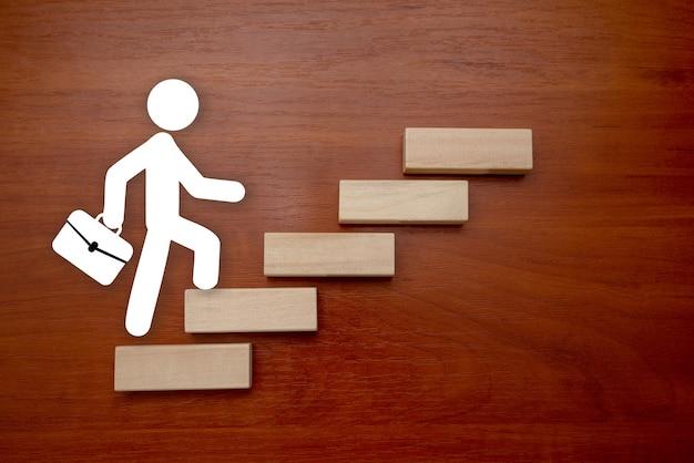 Un uomo d'affari che sale la scala verso il successo in un'immagine concettuale su sfondo in legno. la crescita di un concetto di business e il percorso verso il successo.