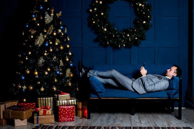 Uomo d'affari in un abito grigio in ufficio alla vigilia di capodanno