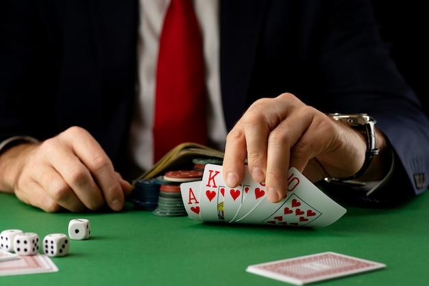 Uomo d'affari al tavolo da gioco verde con fiches, carte e dadi che giocano a poker e blackjack nel casinò