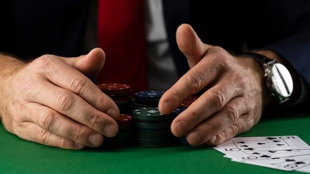 Uomo d'affari al tavolo da gioco verde con fiches e carte che giocano a poker e blackjack nel casinò.