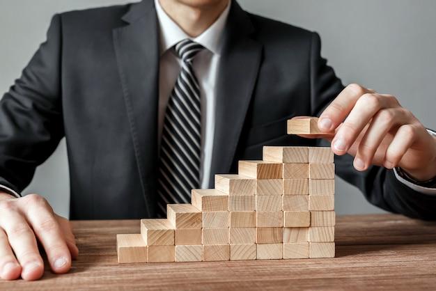 Mano dell'uomo d'affari che organizza lo sviluppo di blocchi di legno di impilamento come scala a gradini. processo, piano e strategia di successo della crescita aziendale nel mondo degli affari.