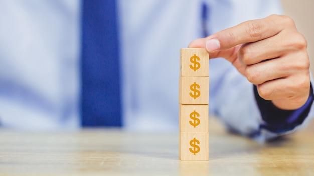 Mano dell'uomo d'affari che sistema blocco di legno con il dollaro dei soldi dell'icona per il concetto di investimento