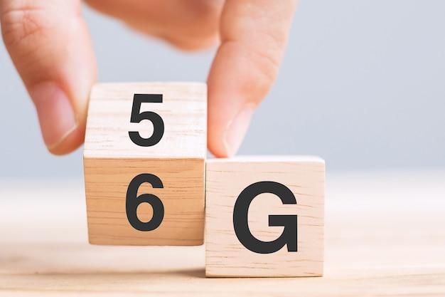 Blocco di legno del cambiamento della mano dell'uomo d'affari da 5g a 6g (generation of cellular mobile communications) tecnologia, rete, social media e concetti digitali