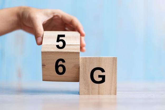 Mano di uomo d'affari cambia blocco di legno dalla tecnologia 5g alla 6g