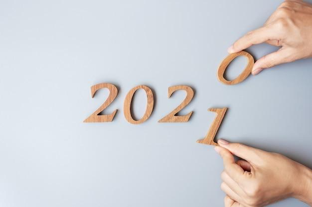 Mano dell'uomo d'affari cambia il numero di legno dal 2020 al 2021
