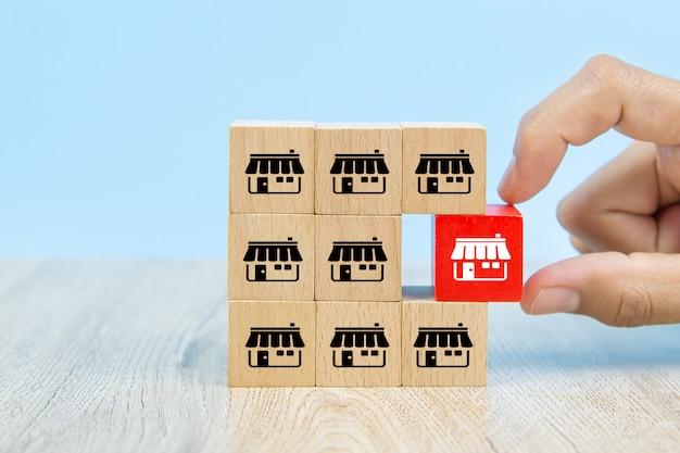 La mano dell'uomo d'affari sceglie il blog di legno del giocattolo di colore del registro impilato con il deposito delle icone di vendita di franchising.