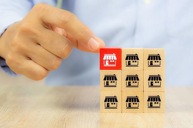Mano di uomo d'affari sceglie blog di giocattoli in legno di colore reg impilati con negozio di icone di marketing in franchising.