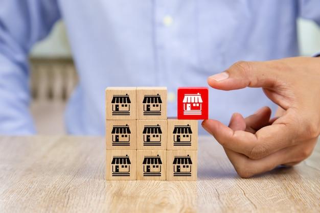 La mano dell'uomo d'affari sceglie il blog di legno con il deposito delle icone di vendita di franchising.