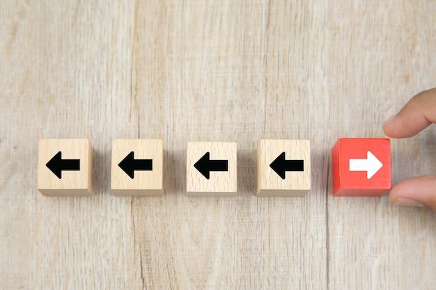 La mano dell'uomo d'affari sceglie il blocco di legno del giocattolo del cubo con le icone della testa della freccia che indicano le direzioni opposte.