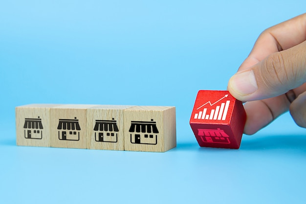 Mano dell'uomo d'affari che sceglie il blog di legno del giocattolo del cubo con l'icona del grafico dal deposito delle icone di vendita di franchising