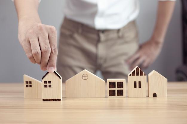 Mano dell'uomo d'affari che sceglie il modello in legno della casa e pianifica di acquistare proprietà