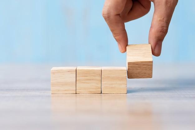 Mano dell'uomo d'affari che lancia blocco di legno sulla tavola