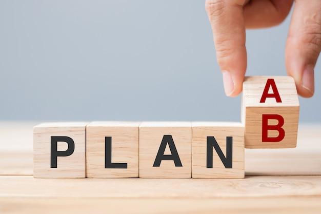 Mano dell'uomo d'affari che lancia blocchi di cubo di legno con piano a modifica al testo piano b sullo sfondo della tabella concetti di strategia, leadership, gestione, marketing, progetto e crisi