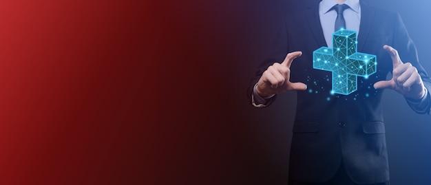 Mano dell'uomo d'affari che tiene 3d più icona poligonale bassa. segno più mezzi virtuali per offrire cose positive come benefici, sviluppo personale, social network profit, assicurazione sanitaria, concetti di crescita.