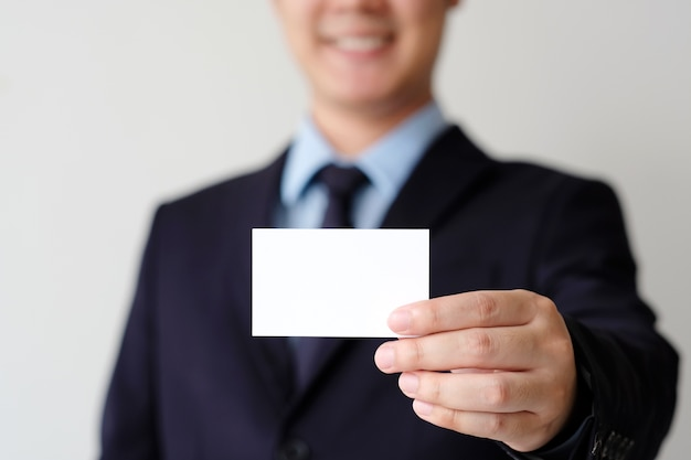 Mano dell'uomo d'affari che tiene biglietto da visita bianco in bianco con lo spazio della copia per testo