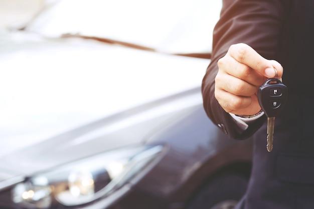 Mano di uomo d'affari che tiene le chiavi della macchina davanti con auto nuove, parcheggio davanti alla casa. concetto di trasporto.