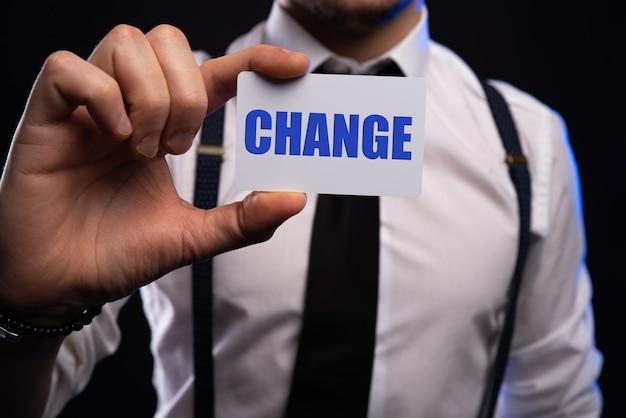 Scheda della holding della mano dell'uomo d'affari con la parola del cambiamento