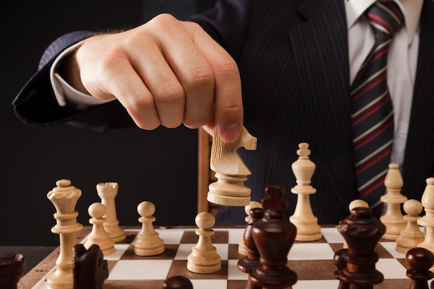 Mano dell'uomo d'affari che tiene un pezzo degli scacchi su una scacchiera